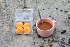 Coffee cup pink plastic and cream puffs in box on the Cement  floor old with copy space.  Royalty Free Stock Photos