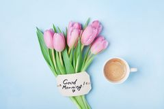 Coffee cup, pink tulip flowers and note good morning on blue table top view. Beautiful breakfast on Mothers or Womans day. Coffee cup, pink tulip flowers and royalty free stock image