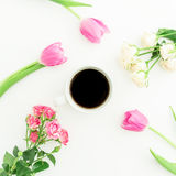 Coffee cup and pink tulips with roses on white background. Flat lay, top view. Stock Images