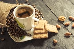 Cup of coffee and biscuits. Coffee cup on a plate and coffee beans pouring out from a burlap sack, biscuits, walnuts and almonds on a wooden table Royalty Free Stock Photography