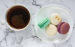 Coffee cup and plate with macarons on marble table background. Delicious coffee break stock photos