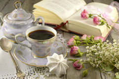Coffee cup with poetry book. Still life with vintage tea set, poetry book and bunch of flowers on wood stock image