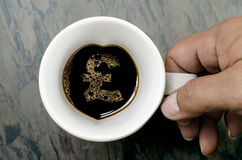 Coffee cup : Pound Sterling sign. A Pound Sterling sign this can serve as a concept for expensive coffee, caffeine addiction etc. and hands holding a cup of hot stock photography