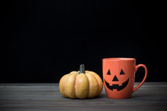 Coffee cup and pumpkin. Halloween concept. Coffee cup as jack o lantern pumpkin on wooden table. Halloween concept stock photo