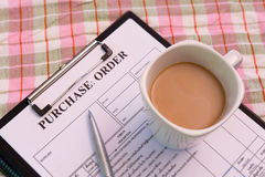 Coffee cup on purchase order form on cloth Royalty Free Stock Photography