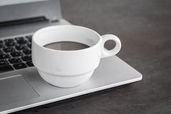 Coffee cup put on laptop Stock Image