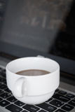 Coffee cup put on laptop Royalty Free Stock Photo