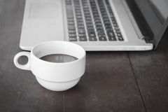 Coffee cup put on laptop Stock Photo