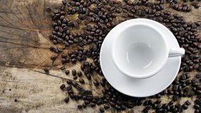 Coffee cup. Put on a wood table with dark roasted coffee beans Royalty Free Stock Image