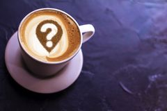 Coffee cup with question mark. In the froth concept for problems, uncertainty and asking questions royalty free stock photo
