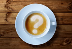 Coffee cup questions. Coffee cup with question mark in the froth concept for problems, uncertainty and asking questions Stock Photos