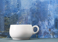 Coffee cup on a rainy day in front of the window Royalty Free Stock Photo