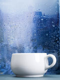Coffee cup on a rainy day in front of the window Royalty Free Stock Image