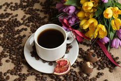 Coffee cup with raw beans on burlap with flower Stock Photo