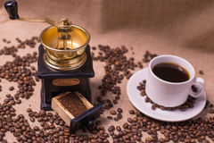 Coffee cup with raw beans on burlap with grinder Royalty Free Stock Images