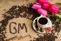Coffee cup with raw beans on burlap with pink tulips Royalty Free Stock Images