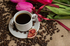 Coffee cup with raw beans on burlap with pink tulips Stock Photos