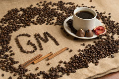 Coffee cup with raw beans on burlap Royalty Free Stock Photo
