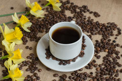 Coffee cup with raw beans on burlap Royalty Free Stock Image