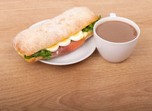 Coffee cup and Real sandwich with smoked salmon, eggs and green on a wooden background. Royalty Free Stock Images