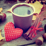 Coffee cup, red heart and autumn still life on table Royalty Free Stock Photo