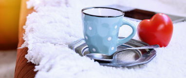 Coffee cup and red heart on white fur Royalty Free Stock Images