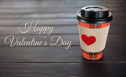 Coffee cup with red heart on wood background. Valentine`s day card Stock Image