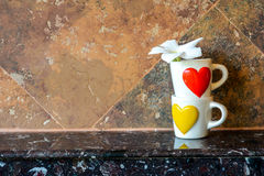 Coffee cup with red heart and yellow heart Stock Image