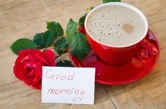 Coffee cup with red rose and notes good morning. Coffee cup with red rose flower and notes good morning on wooden rustic table from above, breakfast on Mothers Stock Images