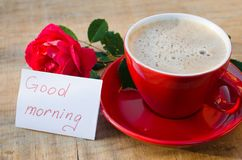 Coffee cup with red rose and notes good morning. Coffee cup with red rose flower and notes good morning on wooden rustic table from above, breakfast on Mothers Stock Photo