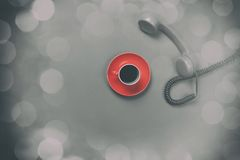 Coffee cup and retro dial phone. Red coffee cup and retro dial phone on grey background Royalty Free Stock Images