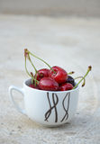 Coffee cup of ripe cherries Royalty Free Stock Photo