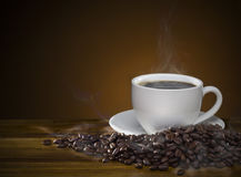 Coffee cup with roasted brown coffee beans and smoke on wooden t. Black hot coffee cup with roasted brown coffee beans and smoke on wooden table. coffee mug with Royalty Free Stock Photo