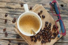 A coffee cup with eyeglass. A coffee cup with roasted coffee beans and the eyeglass on the old wood background royalty free stock photo