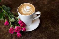 Coffee. Cup of coffee with a rose on a table in a cafe Stock Image