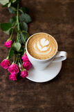 Coffee. Cup of coffee with a rose on a table in a cafe Stock Photos