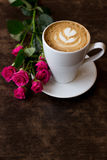 Coffee. Cup of coffee with a rose on a table in a cafe Royalty Free Stock Photos