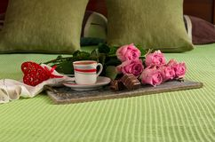 Coffee in a cup and roses on a tray on the bed Royalty Free Stock Photos