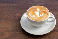 Coffee cup of rosetta latte art on wooden background with copy space Stock Photography