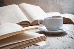 Coffee. Cup of coffee on rustic wooden table with open books royalty free stock images