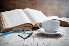 Coffee. Cup of coffee on rustic wooden table with open books stock images