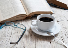 Coffee. Cup of coffee on rustic wooden table with open books royalty free stock image