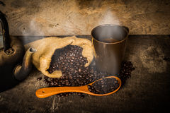 Coffee cup sack scoop of coffee beans and kettle on the old wood Royalty Free Stock Photos