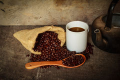 Coffee cup sack scoop of coffee beans and kettle on the old wood Royalty Free Stock Image