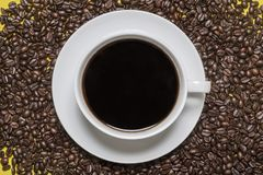 Coffee cup and saucer on a background of coffee beans. Black coffee in a cup and saucer on a background of spilled coffee beans Stock Photography