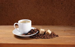 Coffee cup on saucer, beans and sugar Royalty Free Stock Images
