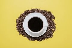 Coffee cup and saucer on a bed of beans. Coffee cup and saucer on a bed of coffee beans on a bright yellow background shot from above Royalty Free Stock Photo