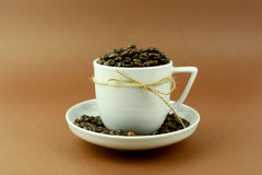 Coffee cup and saucer with a bow and coffee beans.  Royalty Free Stock Photos