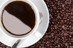 Coffee cup and saucer on coffee beans Royalty Free Stock Photo