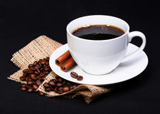 Coffee cup with saucer and coffee beans on burlap over black Royalty Free Stock Images